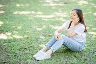 校园草坪上看手机听音乐的女生图片