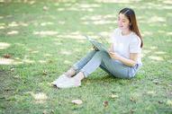 坐在校园草坪上看书的女学生图片