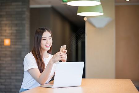 年轻女性拿手机打电话移动办公图片