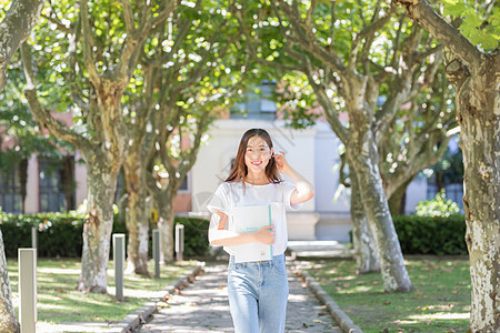 学校里抱着书边走路边撩头发的女同学图片
