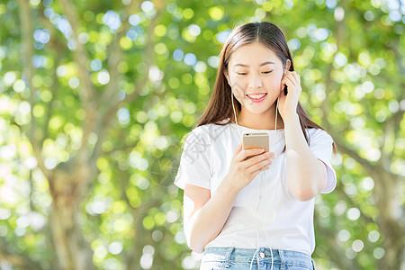 树下用手机听音乐的甜美女生图片