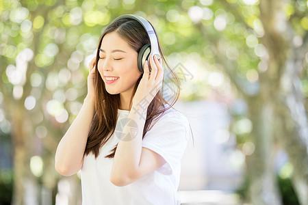 树林下戴耳机听音乐的甜美女生图片
