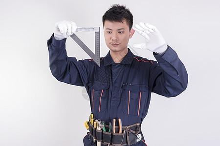 男工人使用三角尺测量动作底图图片