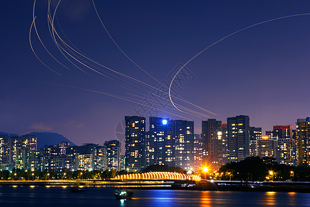 城市夜空上的飞机航道灯轨图片