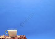 一杯牛奶放在竹篮上图片