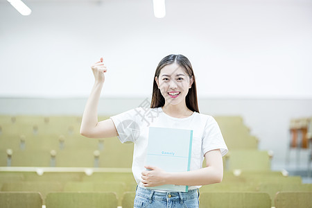 抱着书自信的站在教室里的大学生图片
