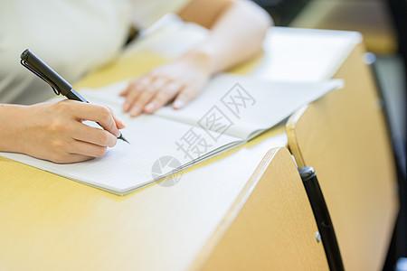 教室手拿钢笔写字特写图片
