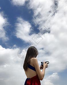 蓝天白云下拿相机的女孩图片