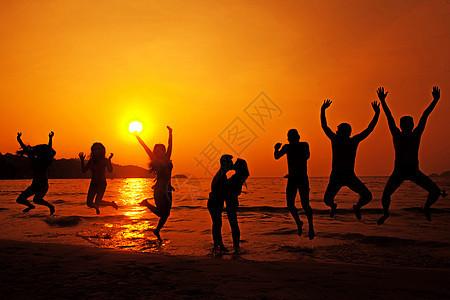 黄昏海边跳跃的人群浪漫剪影图片