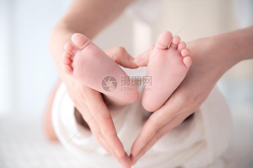 妈妈手环抱婴儿脚丫照片图片