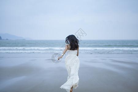 海边奔跑的女性背影图片