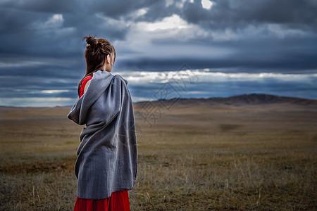 草原上凝望天空的女孩图片