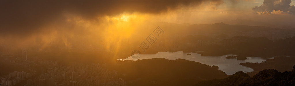 夕阳云层下朦胧的城市水库图片