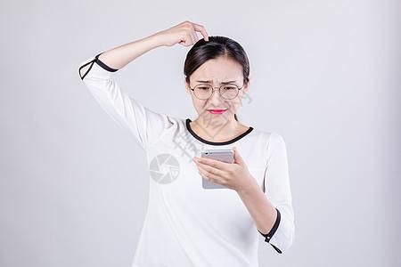 职业女性看手机挠头棚拍图片