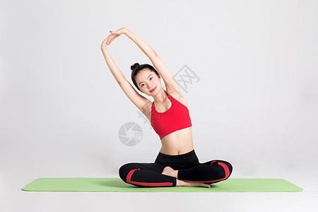 坐在瑜伽垫上做伸展运动的女性图片
