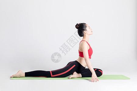 坐在瑜伽垫上做瑜伽动作的女性图片