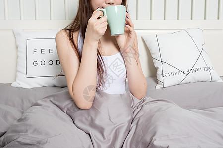 甜美女生坐在床上喝水图片