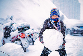 雪中堆雪球玩雪的男孩图片