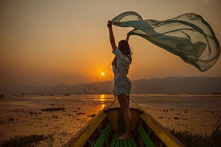 湖面上欣赏日落的美丽女孩图片