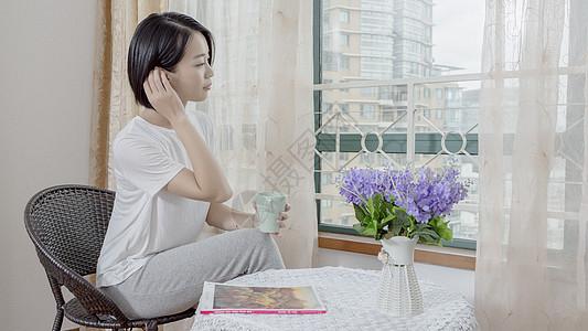 女子在窗边手持水杯休息图片