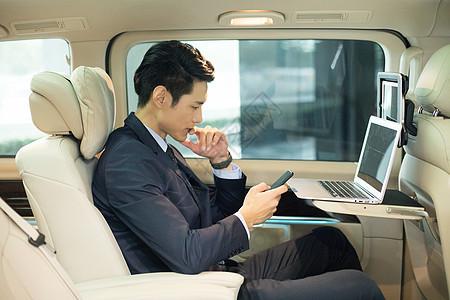 商务男士在汽车上办公图片