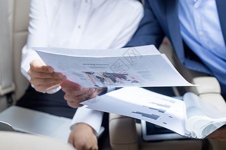 商务人士在商务车内开会看资料图片