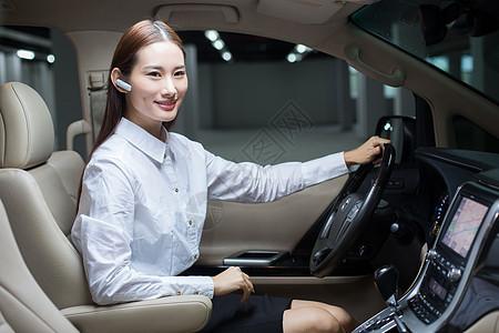 商务女士在商务车内使用蓝牙耳机通话图片