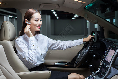 商务女士在商务车内使用蓝牙耳机图片