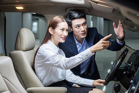 汽车销售在给女士讲解车内构造图片