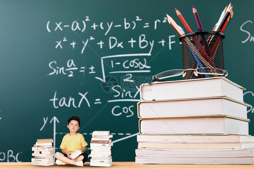 男孩坐在黑板的书上图片