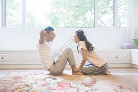 年轻夫妇在客厅做仰卧起坐图片