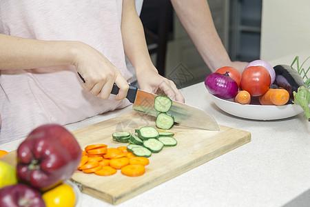 年轻夫妇在厨房切菜手部特写图片