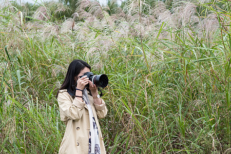 秋天武汉江滩芦苇拿相机少女图片