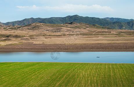 鸭绿江边上的麦田河流山脉图片
