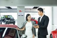 车行销售人员给顾客介绍车型图片
