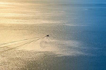 巽寮湾夕阳下海面上高速飞驰的快艇图片