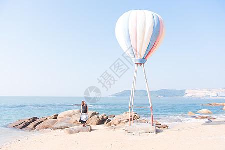 海边热气球旁聆听大海声音的女模特图片