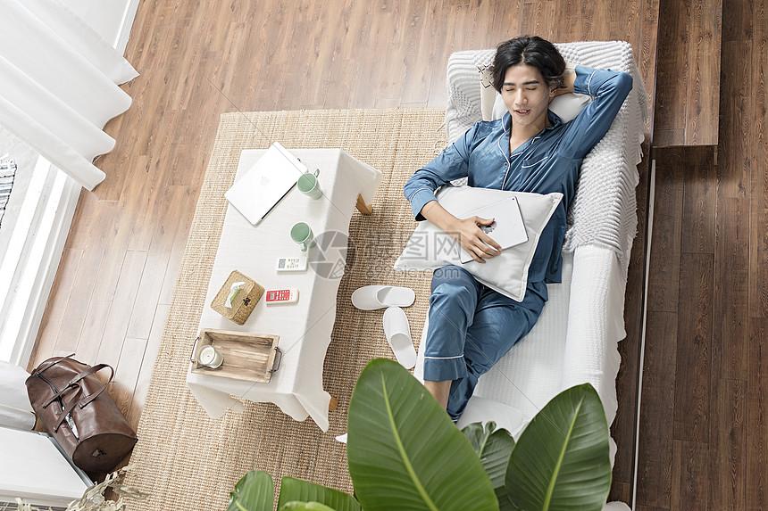 男子在客厅睡觉休息图片