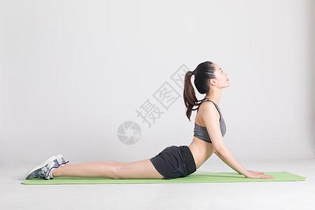 瑜伽垫上做运动动作的年轻女性图片
