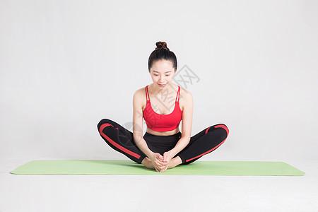 瑜伽垫上做瑜伽动作的年轻女性图片