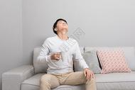 坐在沙发上吃药的男性图片