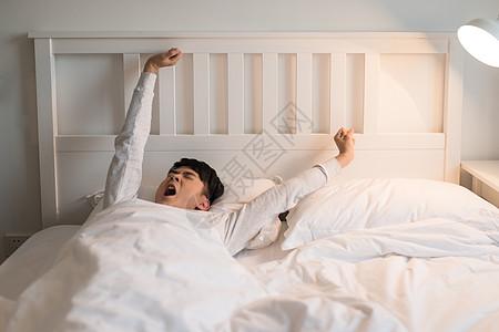 准备起床伸懒腰的年轻男子高清图片