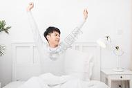 准备起床伸懒腰的年轻男子图片
