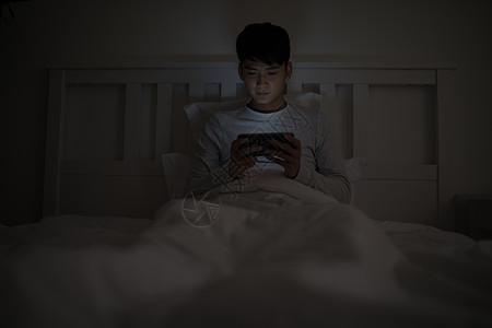 睡前坐在床上玩手机的男子图片