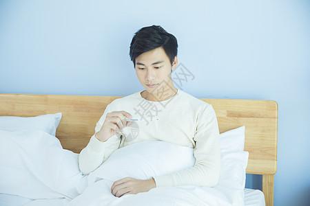躺床上测量体温的年轻男性图片