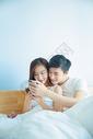 年轻情侣在床上看手机图片