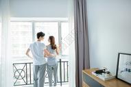年轻情侣在窗边互动图片