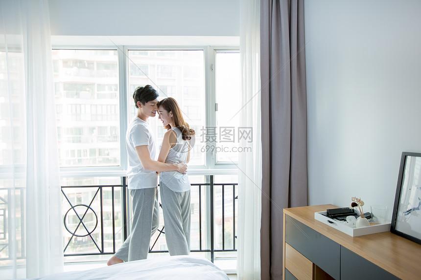 年轻情侣在窗边拥抱图片
