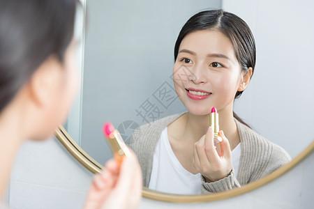 照着镜子画口红的年轻女性图片