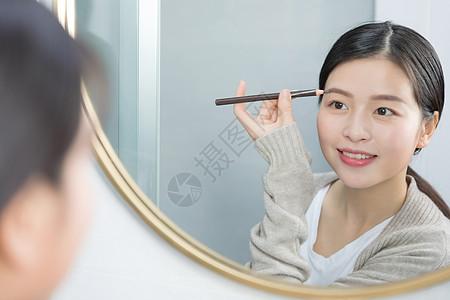 站在镜子前画眉的年轻女性图片